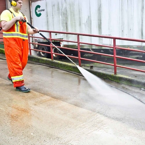 Citywide employee pressure washing concrete ramp